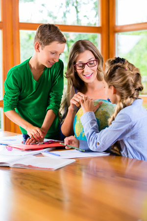 school boy: Homeschooling mother teaching kids private lessons in geography Stock Photo