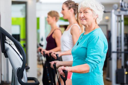 seniors: Personas mayores y jovenes en las placas vibratorias en gimnasio haciendo ejercicios de fitness