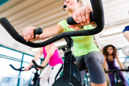 stationary bike: Woman at Fitness Spinning on bike in gym, shot from a low angle