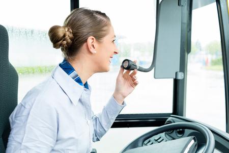 chofer de autobus: Bus Mujer conductor de habla por el micrófono de hacer un anuncio Foto de archivo