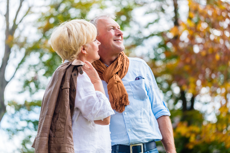 lovingly: Senior couple, husband and wife, embracing each other lovingly in autumn park