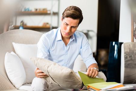 choosing: Man choosing colors and material for furniture in store or showroom browsing through catalog