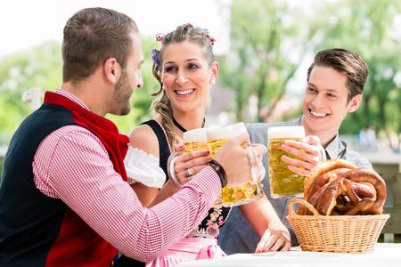 beer garden: Friends in beer garden clinking glasses with beer, pretzel standing on the table