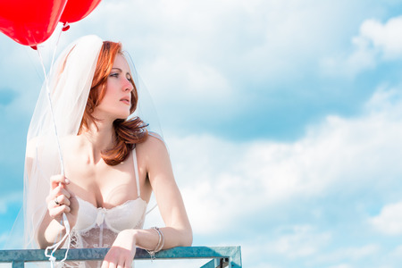 red bra: Bride with red balloons on balcony in lingerie Stock Photo