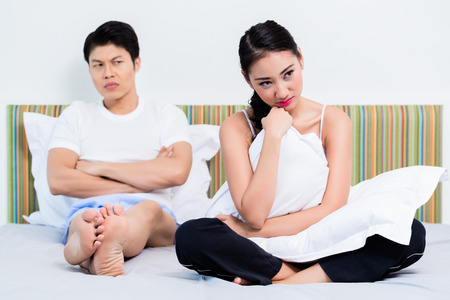 rejecting: Alienated Chinese couple, woman is rejecting her man feeling sad Stock Photo