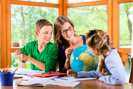 Homeschooling mother teaching kids private lessons in geography Foto de archivo