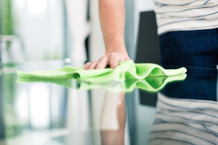 spring cleaning: Man cleaning table in home with cloth