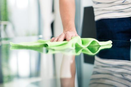 Man schoonmaken tafel in huis met doek