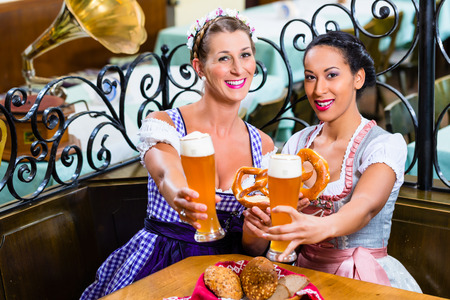 tracht: Girlfriends with Pretzel and Beer in Bavarian Inn eating and drinking Stock Photo