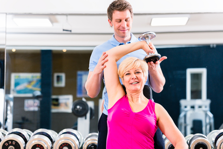 sport fitness: Senior woman at sport exercise with dumbbell in gym with trainer to gain strength and fitness Stock Photo