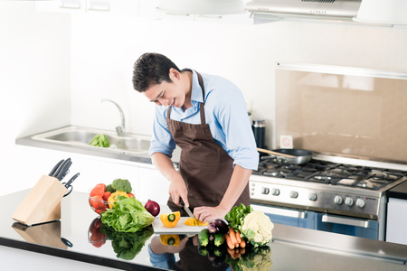 Japanese man preparing salad and cooking in kitchen