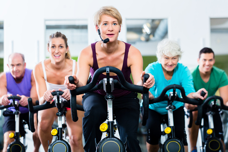 stationary: Senior and young people spinning on fitness bike in gym doing endurance and cardio training, the instructor is leading them on