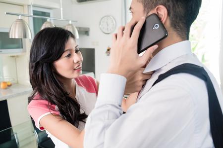 Esposas: El hombre ya se usa el teléfono para los negocios de salir de casa, su esposa es vinculante su corbata como ya es tarde para la oficina