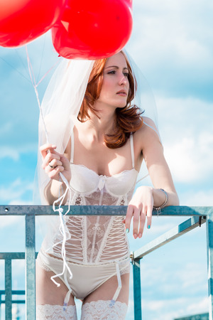 sexy bride: Bride with red balloons on balcony in lingerie Stock Photo