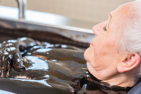 woman bath: Senior woman enjoying mud bath alternative therapy