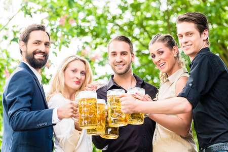 beer garden: Friends or colleagues on beer garden after work toasting with drinks