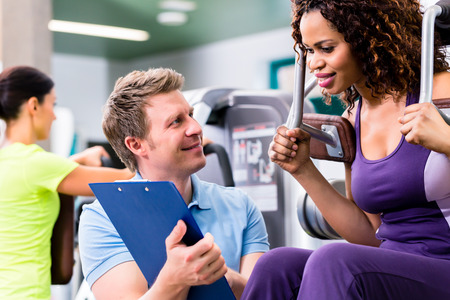 coaches: Fitness training in gym - black woman and personal trainer exercising on resistance machine