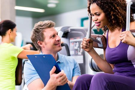 men exercising: Preparación física en el gimnasio - mujer negro y entrenador personal en el ejercicio de la máquina de resistencia Foto de archivo