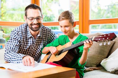 Otec a syn hraje na kytaru doma, dělat hudbu spolu