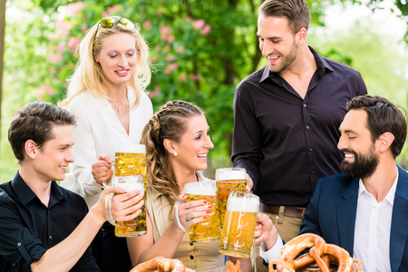 drinks after work: Friends or colleagues on beer garden after work toasting with drinks