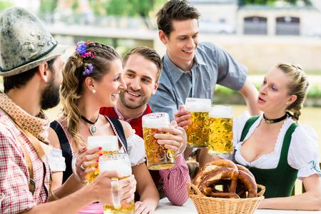 Přátelé v bavorské pivní zahrádce pití v létě Reklamní fotografie