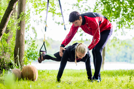 outdoor training: Man and woman at fitness training doing push-ups