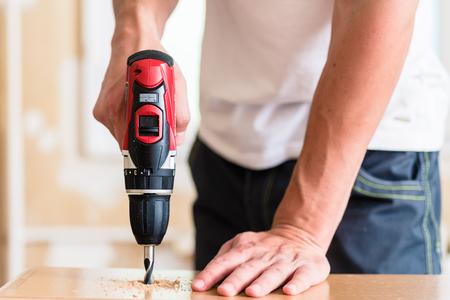 Handwerker oder DIY Mann arbeitet mit Bohrmaschine