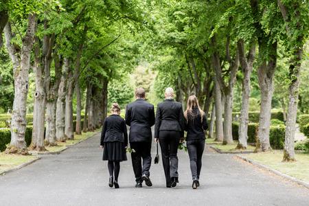 Family walking down alley at graveyard Standard-Bild