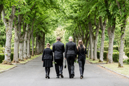 Family walking down alley at graveyard Stockfoto