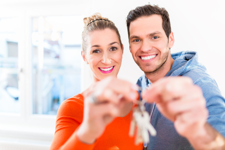 home keys: Woman and man holding proudly home or house key Stock Photo