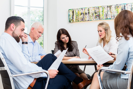 law office: Lawyers having team meeting in law firm reading documents