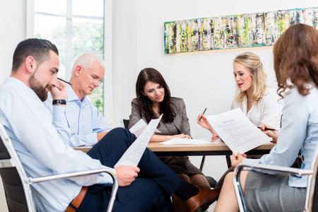 negociacion: Los abogados que tienen reunión del equipo en los documentos de lectura bufete de abogados Foto de archivo
