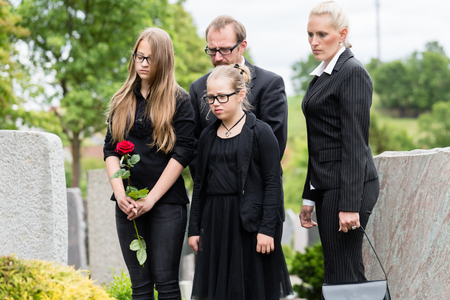 Family on cemetery or graveyard mourning deceased relative Stockfoto