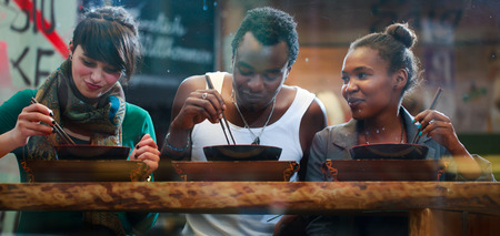 three friends: Man and women, black and Latin people, eating late in Korean eatery Stock Photo