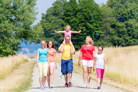 caminar: Familia que tiene caminata en la ruta en verano bajo el sol