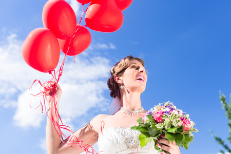 helium: Bride at wedding with read helium balloons Stock Photo