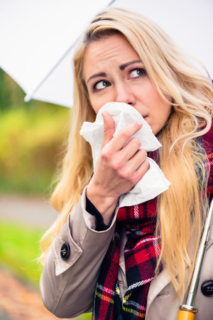 running nose: Woman having cold or flu due to bad autumn weather