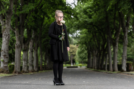 graveyard: girl with white rose mourning deceased on graveyard being an orphan now Stock Photo
