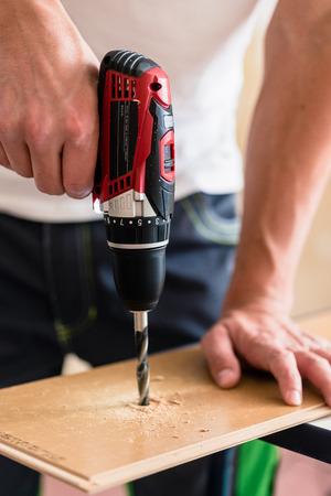 carpintero: Artesano u hombre DIY trabajar con taladro eléctrico