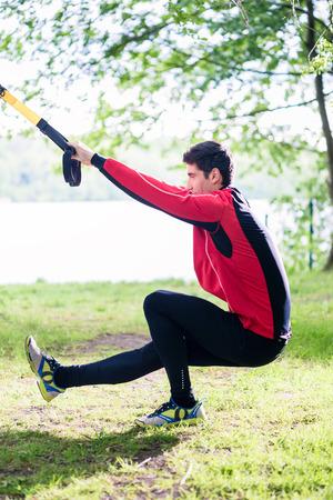 slings: Man doing fitness leg training with slings