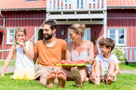 water melon: Family sitting in grass front of home eating water melon Stock Photo