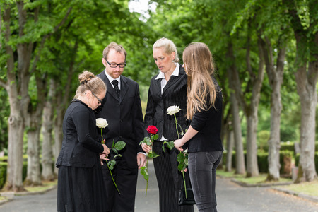 Family mourning on funeral at cemetery standing in group with flowers