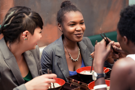 noodle soup: Friends, black and Latin people, eating ramen noodle soup in Japanese Restaurant