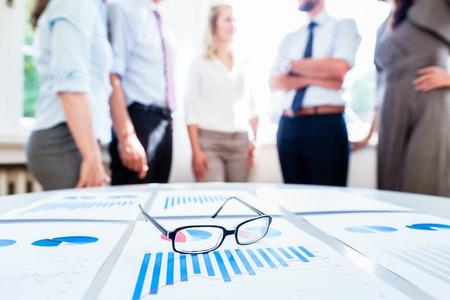 Geschäftsleute im Büro mit Finanzdaten auf dem Schreibtisch zur Analyse bereit