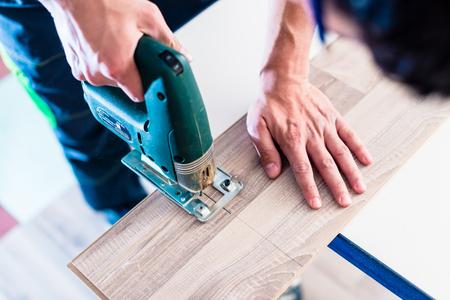 DIY pracovník řezání dřeva panel s přímočarou pilu Reklamní fotografie