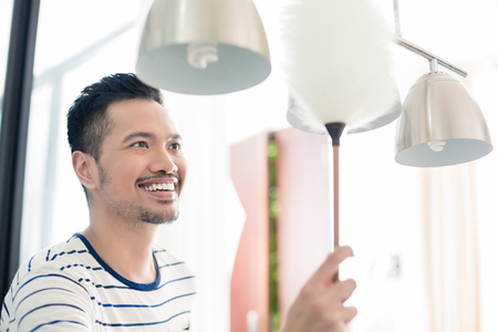 dusting: Asian man dusting his home using duster on lamp Stock Photo