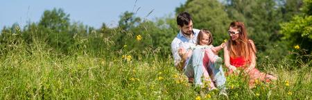 Cuadro del panorama de la familia con la madre, padre e hija en la pradera
