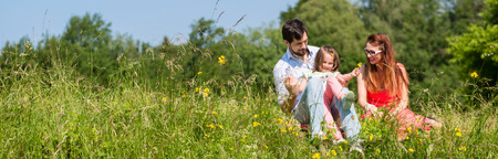 Panorama picture of family with mom, dad and daughter on meadow Standard-Bild
