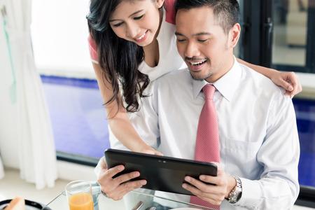 correo electronico: Asia pareja de desayunar antes que el hombre va a la oficina, que es el control de los mensajes de correo electr�nico o noticias con su esposa Foto de archivo