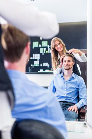 cutting hair: Haircutter cutting hair, shot in mirror